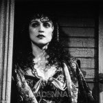 1992:  American singer and actor Madonna stands in a doorway while looking off camera in a scene from director Woody Allen's film, 'Shadows and Fog,' in which she starred.  Madonna wears a curly wig and a dress with a plunging neckline.  RESTRICTED.  PLEASE INQUIRE.  (Photo by Brian Hamill/Getty Images)